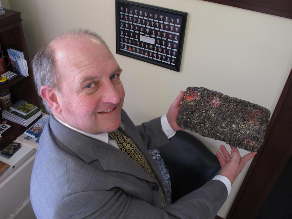 FILE - In this Feb. 7, 2012, file photo, Idaho State Rep. Eric Anderson poses in his offices in the Idaho Capitol in Boise with an Idaho license plate he left for six months in Lake Mead near Las Vegas to be encrusted with quagga mussels. A regional power planning group from Idaho, Oregon, Washington and Montana is pursuing $2 million from the federal government to help fend off the menace of invasive mussels that have clogged Colorado River reservoirs since 2007. These states and others say they're frustrated by the number of boats that continue to come from Lake Mead in Nevada and Arizona over their borders infested with quagga and zebra mussels. (AP Photo/John Miller, File)