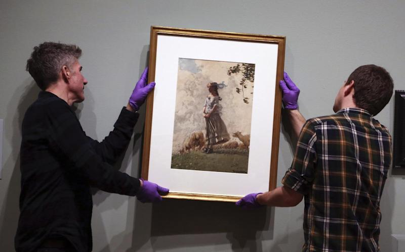 "In this Tuesday Feb. 21, 2017 photo, installations technicians Eric Griffin, left, and Gus Boyce hang Fresh Air by Winslow Homer at the Philadelphia Museum of Art in Philadelphia. ""American Watercolor in the Age of Homer and Sargent"" will be on view from March 1 to May 14, 2017, bringing together masterpieces drawn from public and private collections throughout the county, and will be shown only in Philadelphia. (AP Photo/Jacqueline Larma)"