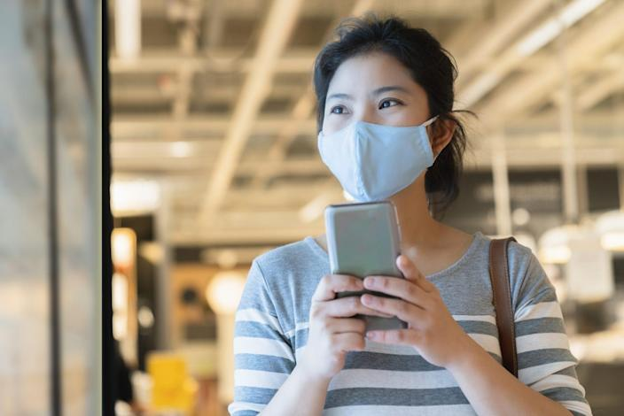 new normal after covid19 epidemic smart asian female wear protection mask hand use smartphone communication in department store new lifestyle abstract blur background.