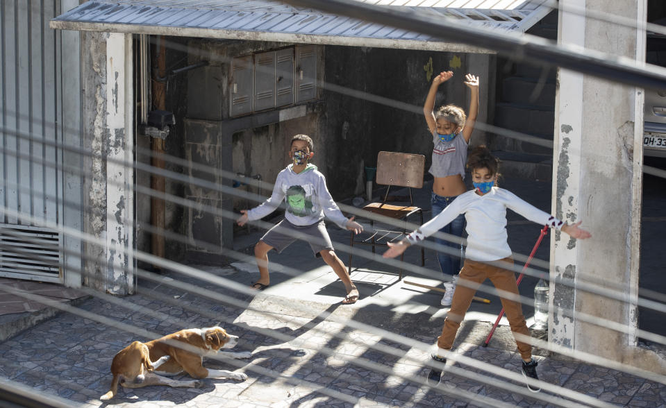 Children exercise from the rooftop of their building during and outdoor workout class imparted by physical trainer Ivan Nascimento for his neighbors during a quarantine imposed by the state government to help contain the spread of the new coronavirus in the Brasilandia neighborhood of Sao Paulo, Brazil, Sunday, May 17, 2020. (AP Photo/Andre Penner)