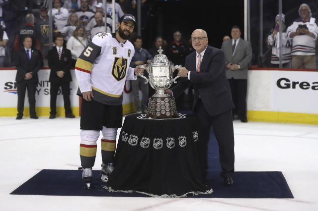 Vegas Golden Knights' Deryk Engelland (5) accepts the Clarence S. Campbell Bowl from Deputy Commissioner Bill Daly after defeating the Winnipeg Jets during Western Conference Finals, game 5, in Winnipeg, Sunday, May 20, 2018. (Trevor Hagan/The Canadian Press via AP)