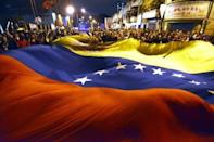 Supporters of Venezuelan President Hugo Chavez wave a huge national flag outside the Military Hospital in Caracas, on March 5, 2013