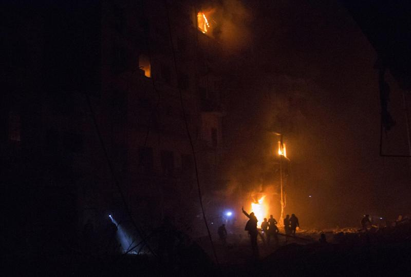 Syrians try to rescue wounded people from a burning building following a reported airstrike by government forces on the Kalasa neighbourhood of the northern Syrian city of Aleppo on November 12, 2014 (AFP Photo/Karam Al-Masri)
