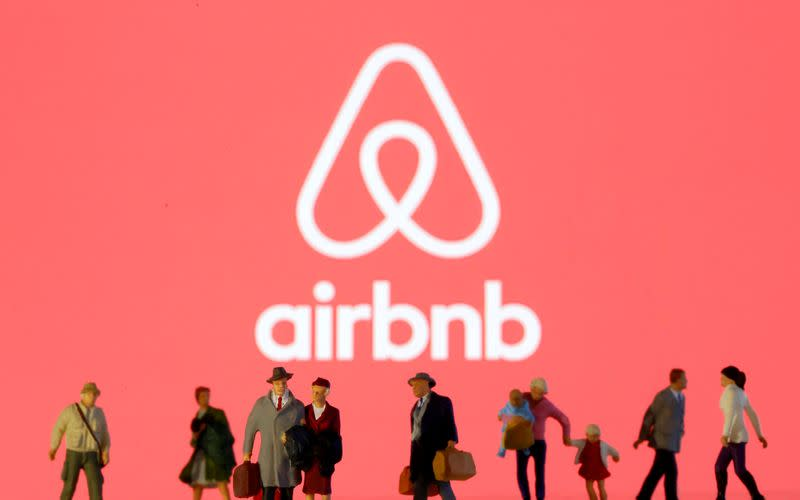 FILE PHOTO: Small toy figures are seen in front of diplayed Airbnb logo