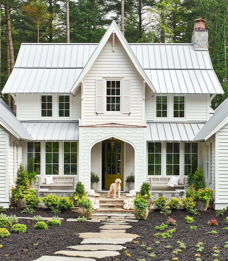 """<p>On the exterior of our 2020 Idea House, a coat of Sherwin-Williams <a href=""""https://www.sherwin-williams.com/homeowners/color/find-and-explore-colors/paint-colors-by-family/SW6418-rural-green"""" rel=""""nofollow noopener"""" target=""""_blank"""" data-ylk=""""slk:Rural Green (SW 6418)"""" class=""""link rapid-noclick-resp"""">Rural Green (SW 6418)</a> on the front door pops against the bright white siding, painted <a href=""""https://www.sherwin-williams.com/homeowners/color/find-and-explore-colors/paint-colors-by-family/SW7006-extra-white"""" rel=""""nofollow noopener"""" target=""""_blank"""" data-ylk=""""slk:Quill Extra White (SW 7006)"""" class=""""link rapid-noclick-resp"""">Quill Extra White (SW 7006)</a>. See more <a href=""""https://www.southernliving.com/home/idea-houses/2020-idea-house-tour"""" rel=""""nofollow noopener"""" target=""""_blank"""" data-ylk=""""slk:here"""" class=""""link rapid-noclick-resp"""">here</a>.</p>"""