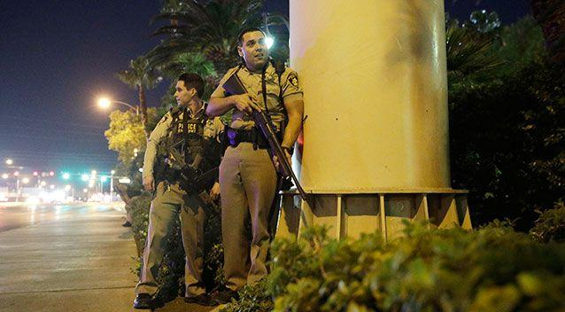 Police officers take cover near the scene of the shooting. Source: AAP