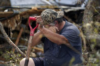 "Bradley Beard wipes his face as he rests while he searches in vain for his water shutoff valve, next to his heavily damaged home and the destroyed trailer home of his daughter Nicole in Hackberry, La., in the aftermath of Hurricane Laura, Saturday, Aug. 29, 2020. ""This is too much for a 62 year old man,"" he said."" (AP Photo/Gerald Herbert)"