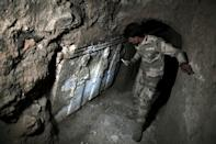 A member of the Iraqi military inspects artefacts in a tunnel dug by the Islamic State (IS) group near Mosul