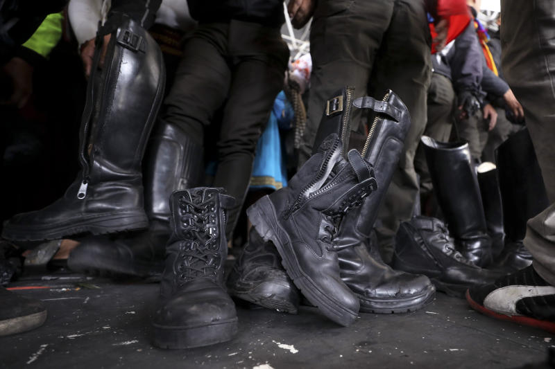 Police officers detained by anti-government protesters are forced to remove their boots on the stage at the Casa de Cultura in Quito, Ecuador, Thursday, Oct. 10, 2019. Indigenous demonstrators in Ecuador are holding captive at least eight police officers following anti-government protests. Ecuador's indigenous groups are gathering for more protests against the removal of fuel subsidies, a step announced by President Lenín Moreno last week. (AP Photo/Fernando Vergara)