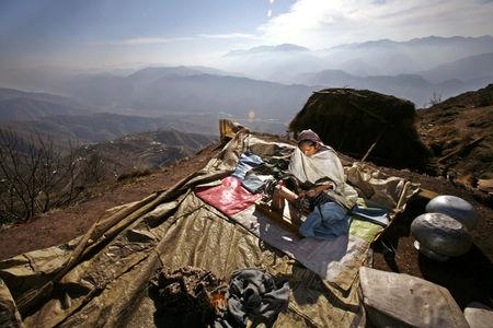 FILE PHOTO: A Kashmiri earthquake survivor uses her sewing machine to sew up winter clothes, outside her shelter on the mountainous Buttlian area, some 25 km northeast of the earthquake-devastated city of Muzaffarabad in Pakistan-administered Kashmir, January 26, 2006. REUTERS/Yannis Behrakis/File photo