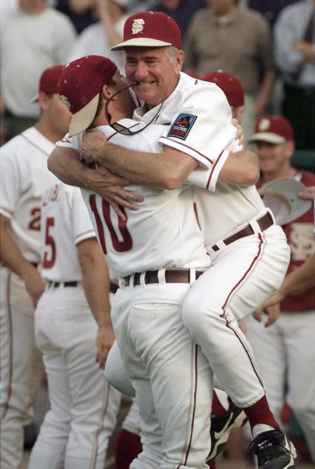 FILE - In this June 18, 1999, file photo, Florida State coach Mike Martin leaps into the arms of pitcher Chris Chavez after the Seminoles defeated Stanford 14-11 on a home run in the 13th inning at the College World Series in Omaha, Neb. Mike Martin has seen college baseball grow nationally in his 39 seasons as Florida States coach. His success leading the Seminoles though has remained a constant. Martin, who has 1,974 wins, needs three more to pass Augie Garrido for the most victories in NCAA baseball history. He could get the milestone this weekend when Florida State hosts Miami in a three-game series, April 27-29, 2018, in Tallahassee. (AP Photo/Rodney White, File)