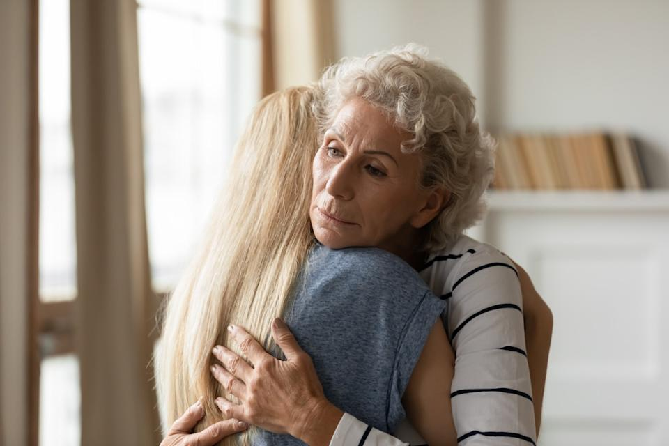 Young empathic woman embracing soothing comforting frustrated older mature mother. Grownup daughter apologizing to offended middle aged mommy. Two female generations family overcoming grief together.