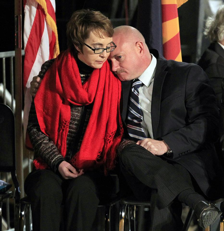 Mark Kelly leans on the shoulder of his wife, U.S. Rep. Gabrielle Giffords, at a memorial vigil remembering the victims and survivors of the shooting that wounded Giffords, 12 others and killed six one year ago Sunday, Jan. 8, 2012, in Tucson, Ariz. (AP Photo/Ross D. Franklin)