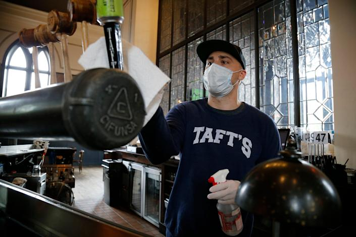 Staff member Sam Perna cleans and sanitizes surfaces on the first day of in-door dining since the statewide ban was lifted at Taft's Ale House in the Over-the-Rhine neighborhood of Cincinnati on Thursday, May 21, 2020.