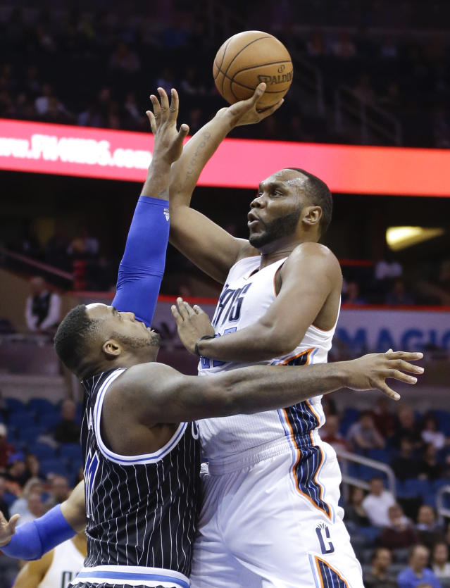Charlotte Bobcats' Al Jefferson, right, makes a shot over Orlando Magic's Glen Davis in the first half of an NBA basketball game in Orlando, Fla., Friday, Jan. 17, 2014.(AP Photo/John Raoux)