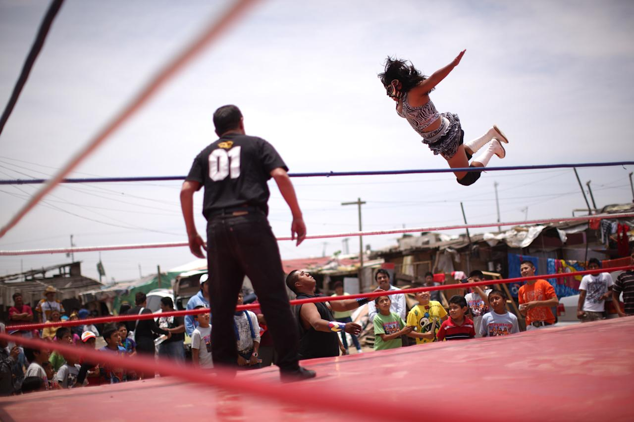 In this photo taken May 20, 2012, Mexican Lucha Libre wrestler Shitara jumps over Black Machine during a Caravan Super Tarin traveling wrestling show on the outskirts of Mexico City. The caravan brings Mexico's Lucha Libre wrestling to the capital's poorest neighborhoods, giving free performances to those who don't have the money to buy a 300 pesos ($22) ticket to see a professional wrestling event at one of Mexico City's big arenas. (AP Photo/Alexandre Meneghini)