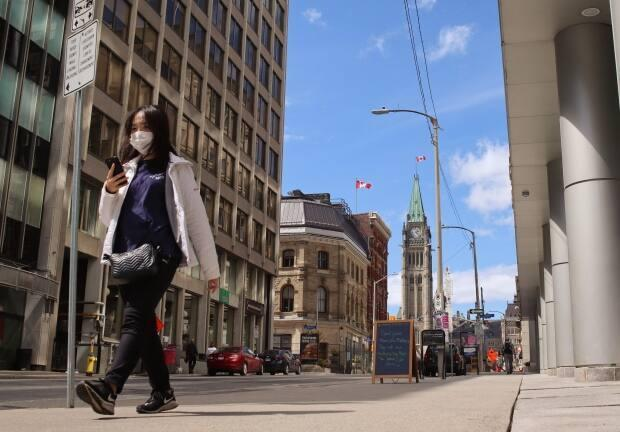 A woman checks her phone while walking through downtown Ottawa on May 2, 2021, during the third wave of the COVID-19 pandemic. (Trevor Pritchard/CBC - image credit)