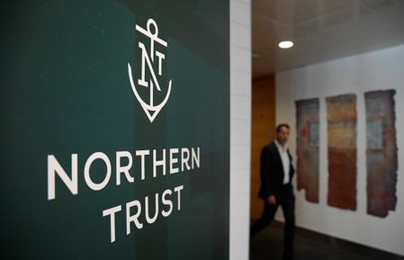An employee walks past a company logo at Northern Trust offices in London