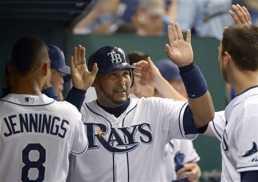 Tampa Bay Rays' Jose Molina, center, is congratulated by teammates Desmond Jennings, left, and Ben Zobrist after scoring on a hit by B.J. Upton during the fifth inning of a baseball game against the Oakland Athletics in St. Petersburg, Fla., Friday, Aug. 24, 2012.(AP Photo/Phelan M. Ebenhack)