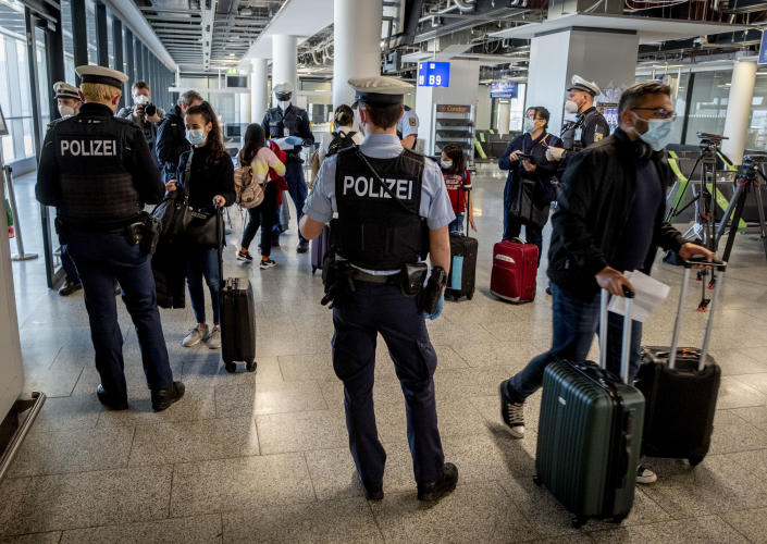 FILE - In this March 30, 2021, file photo, German federal police officers check passengers arriving from Palma de Mallorca for a negative Corona test as they arrive at the airport in Frankfurt, Germany. Germany will require people entering the country who haven't been vaccinated or recently recovered from COVID-19 to show a negative test result starting from Sunday. (AP Photo/Michael Probst, File)