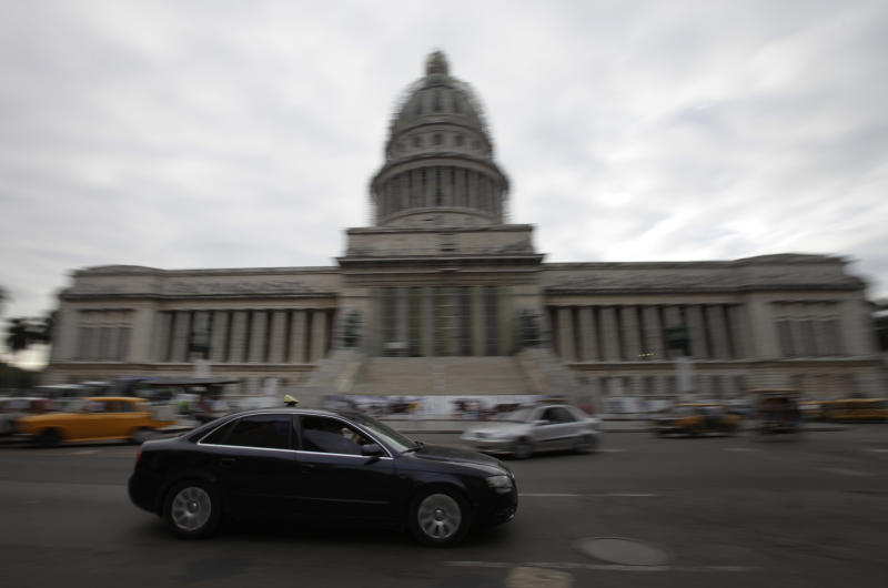 An automobile drives by the Capitol in Havana, Cuba, Thursday, Dec. 19, 2013. According to official media the government is opening the automobile market by eliminating the special permit that strictly limited the number of people allowed to buy vehicles from the state. (AP Photo/Franklin Reyes)