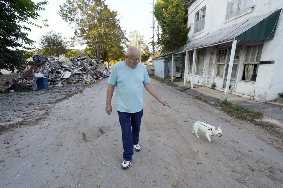 Tommy Goodwin walks his dog, Tasha, down a street lined with flood-damaged buildings and piles of debris Sept. 27, 2021, in Waverly, Tenn. After a devastating flood hit Aug. 21, the town of just over 4,000 people faces a dilemma. More than 500 homes and 50 businesses were damaged. That will likely result in massive revenue losses while the city spends millions on cleanup and repairs. If those homes and businesses don't return, the town could die a lingering death. But if they build back along the creek, they could be risking another disaster. (AP Photo/Mark Humphrey)