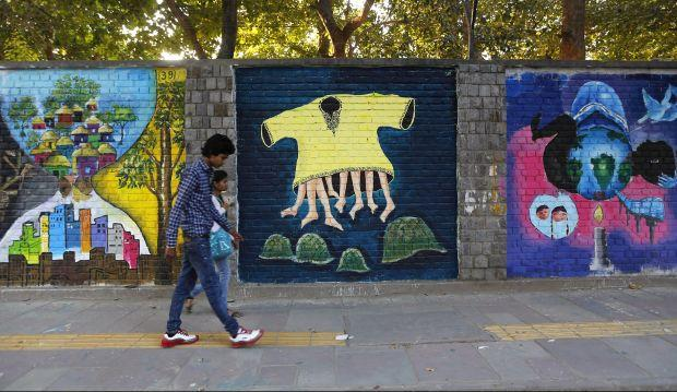 """Commuters walk past graffiti themed """"Design the Change"""" on a wall of the University of Delhi campus"""