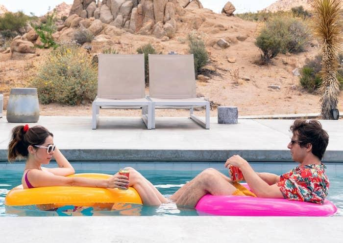 Cristin Milioti and Andy Samberg drinking on floaties in a pool