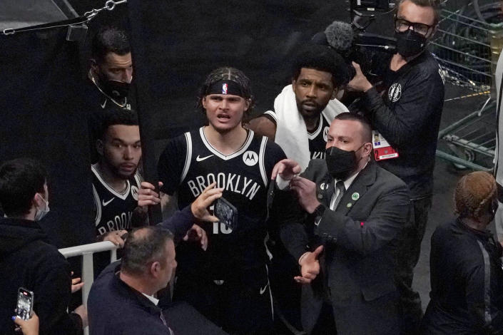 FILE - A security guard points as Brooklyn Nets' Kyrie Irving, right with towel, and teammates look up at a fan who reportedly threw a water bottle at him as he left the court after Game 4 during an NBA basketball first-round playoff series in Boston, in this Sunday, May 30, 2021, file photo. Mindful of high-profile incidents of unruly fan behavior in recent years, the NBA has partnered with the National District Attorneys Association to connect franchises with prosecutors who can serve as points of contact with teams when misconduct occurs. (AP Photo/Elise Amendola, File)