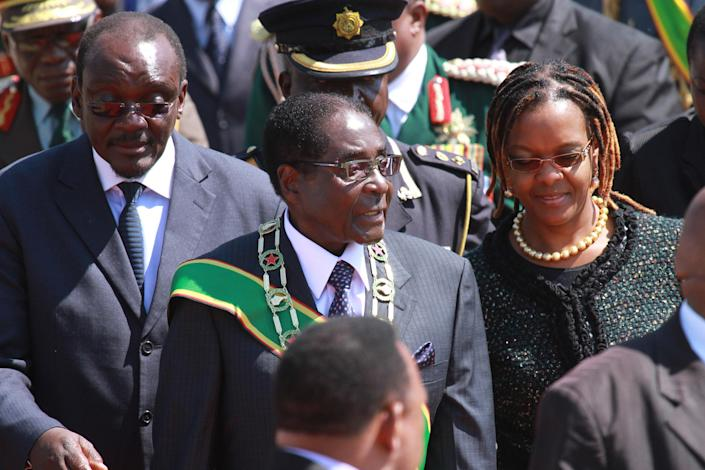 Zimbabwean President elect Robert Mugabe and his wife Grace, right, arrive at the country's Commemoration of Heroes day in Harare, Zimbabwe Monday, Aug. 12, 2013. Mugabe received more than 60 percent of the vote in just-ended Presidential elections while his main challenger Morgan Tsvangirai is challenging the results in court and declaring the election null and void. (AP Photo/Tsvangirayi Mukwazhi)