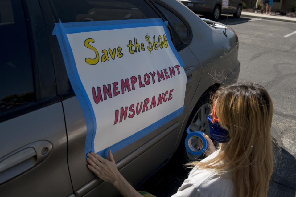 Francis Stallings tapes signs to her car before participating in a caravan rally down the Las Vegas Strip in support of extending the $600 unemployment benefit, August 6, 2020, in Las Vegas, Nevada.(Photo by BRIDGET BENNETT/AFP via Getty Images)