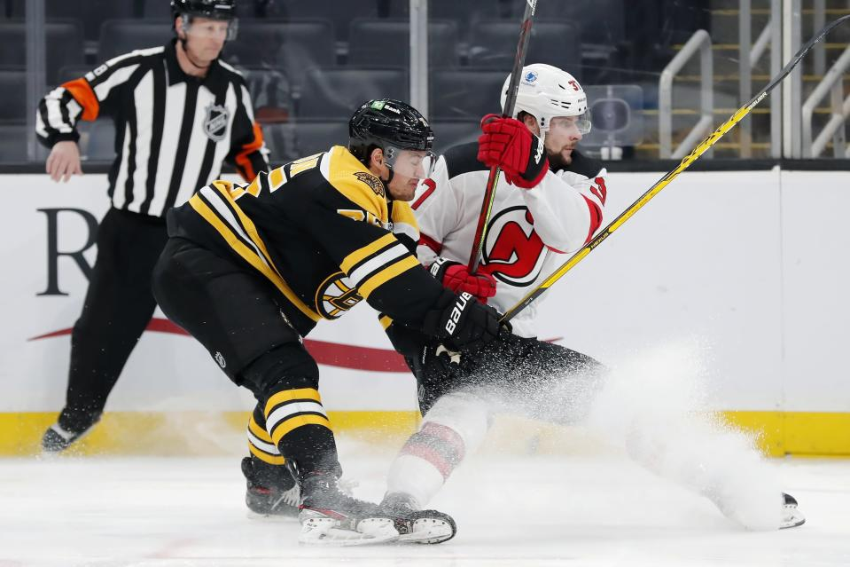 Boston Bruins' Connor Clifton (75) and New Jersey Devils' Pavel Zacha (37) battle for the puck during the first period of an NHL hockey game, Sunday, March 7, 2021, in Boston. (AP Photo/Michael Dwyer)