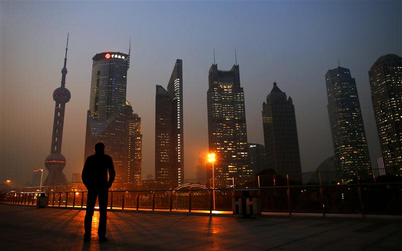 Man looks at the Pudong financial district of Shanghai