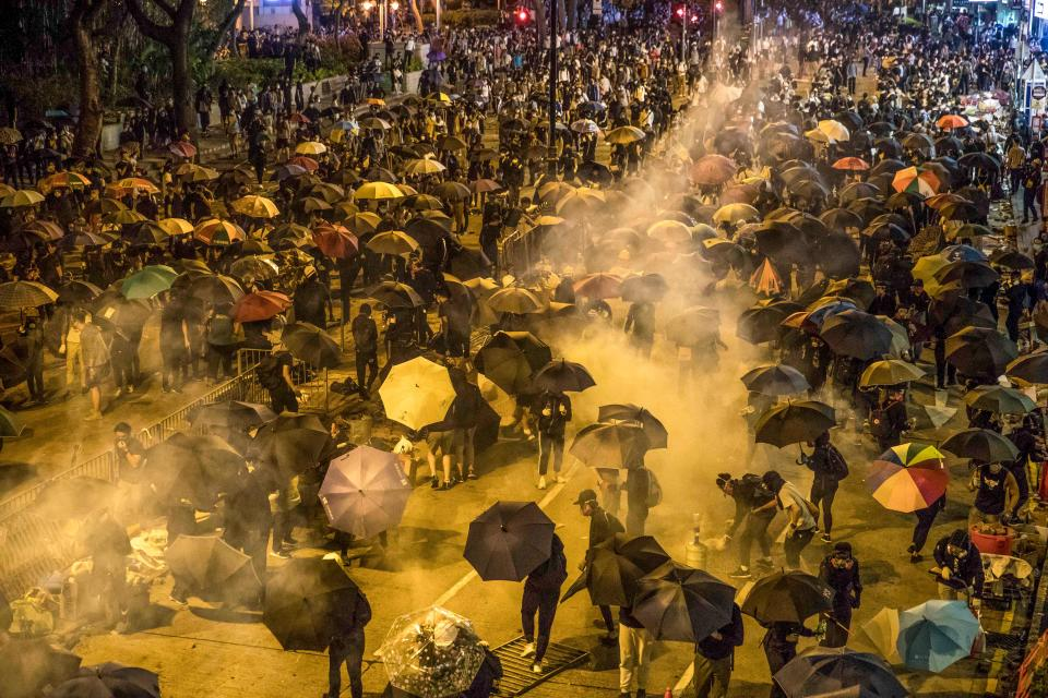 Protesters react as police fire tear gas while they attempt to march towards Hong Kong Polytechnic University in Hung Hom district of Hong Kong on November 18, 2019. - Dozens of Hong Kong protesters escaped a two-day police siege at a campus late on November 18 by shimmying down a rope from a bridge to awaiting motorbikes in a dramatic and perilous breakout that followed a renewed warning by Beijing of a possible intervention to end the crisis engulfing the city. (Photo by DALE DE LA REY / AFP) (Photo by DALE DE LA REY/AFP via Getty Images)