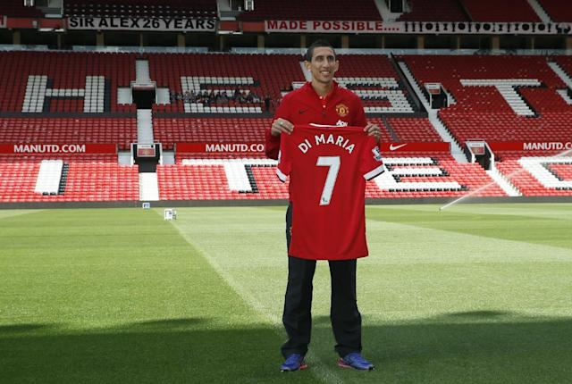 Manchester United's new player Angel Di Maria poses for photographers holding his new shirt, at Old Trafford Stadium in Manchester, England, Thursday, Aug. 28, 2014. Manchester United have signed winger Angel Di Maria from Real Madrid for a British record transfer fee of 59.7m. The Argentine winger had a medical in Manchester on Tuesday and has signed a five-year deal. (AP Photo/Alastair Grant)