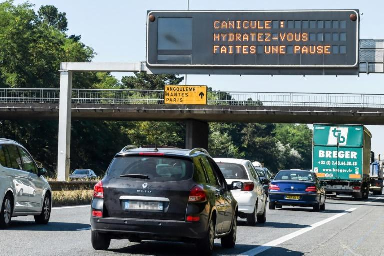 "A road sign displays the message ""heatwave warning, hydrate yourself and take breaks"" near Bordeaux, southwestern France as a heatwave continues to bake Europe"