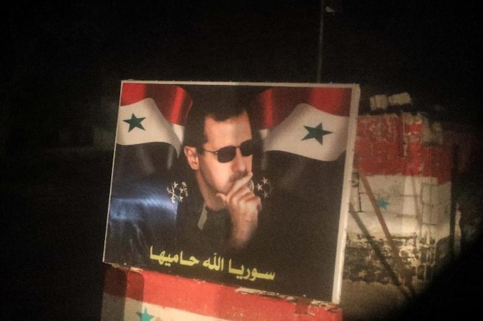 A poster of Syrian President Bashar al-Assad is seen at a checkpoint in the city of Tartus on April 2, 2018 (AFP Photo/Abdullah HAMMAM)