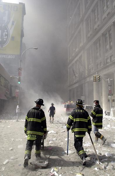 Firemen make their way through rubble and debris after the collapse of one of the World Trade Center Towers in New York on September 11, 2001 (AFP Photo/Stan Honda)
