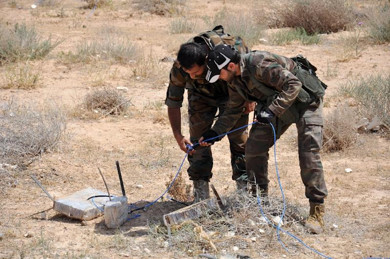 Syrian army soldiers attempt to defuse an improvised explosive device (IED) in northeastern Palmyra on May 17, 2015 (AFP Photo/)