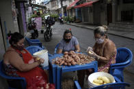 Women peel potatoes outside a snack bar amid the new coronavirus pandemic in Rio de Janeiro, Brazil, Friday, Oct. 9, 2020. Many people in Brazil are struggling to cope with less pandemic aid from the government and jumping food prices, with millions expected to slip back into poverty. (AP Photo/Silvia Izquierdo)