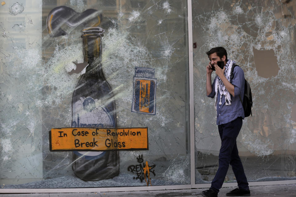An anti-government protester speaks on a mobile phone as walks in front of a shop that damaged by protesters in the aftermath of a protest against the Lebanese government in Beirut, Lebanon, Monday, Oct. 21, 2019. Protesters have closed major roads around Lebanon ahead of an emergency Cabinet meeting to discuss a rescue plan for the country's crumbling economy. AP Photo/Hassan Ammar)