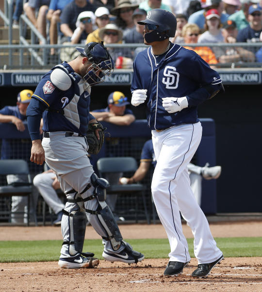 San Diego Padres' Manny Machado cross the plate after hitting a two-run home run as Milwaukee Brewers catcher Manny Pina looks away during the first inning of a spring training baseball game, Wednesday, March 20, 2019, in Peoria, Ariz. (AP Photo/Matt York)