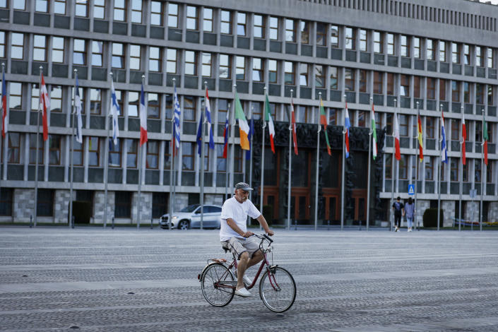 A cyclist rides past the European flags in front of the Slovenia Parliament building in Ljubljana, Slovenia, Tuesday, June 29, 2021. Slovenia takes over the European Union presidency with its Prime Minister in the focus because of his squabbles with Brussels, alliance with populist Hungarian leader Viktor Orban and increasingly autocratic policies. All of these are casting doubt on the small country's credibility to lead the 27-nation bloc. Although the rotating 6-month EU Council presidency, which Slovenia assumes from Portugal on Thursday, is mostly bureaucratic and to an extent symbolic, it comes amid the bloc's painful post-COVID-19 recovery, the stalled EU enlargement process and concerns that the leadership role could be used by the government to further obstruct media freedoms in Slovenia and elsewhere in Europe. (AP Photo)