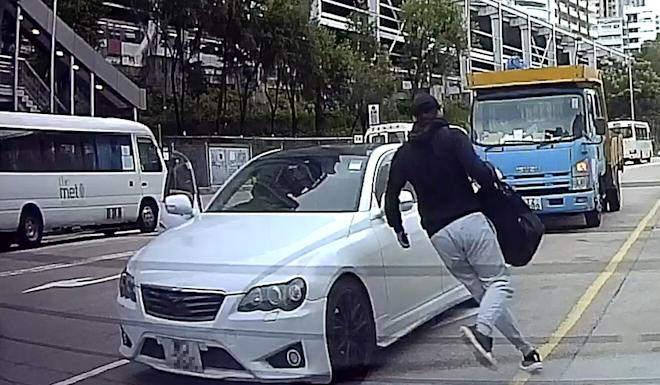 A man runs toward what police believe was the getaway vehicle used in an August 4 assault and robbery that saw a HK$270,000 Rolex stolen. Photo: Facebook