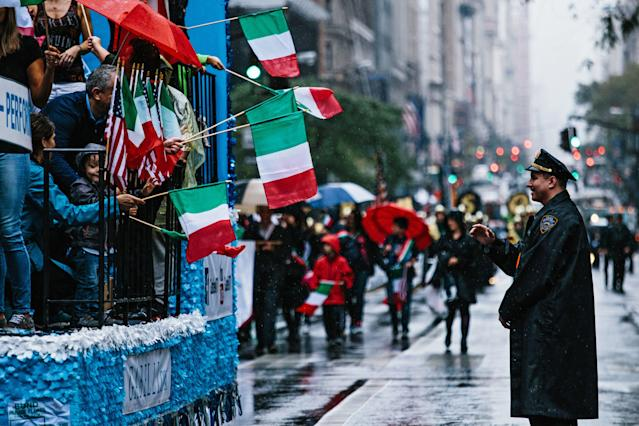 <p>A police officer (R) looks as people with Italian flags march Fifth Avenue during the 73rd Annual Columbus Day Parade in New York, Oct. 9, 2017, celebrating the anniversary of Christopher Columbus's arrival in the Americas in 1492. (Photo: Alba Vigaray/EPA-EFE/REX/Shutterstock) </p>