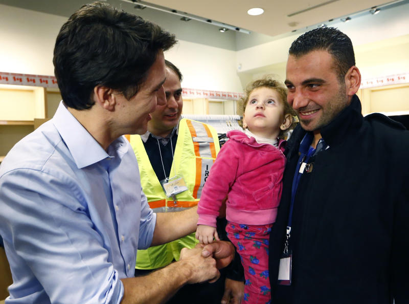 Syrian refugees are greeted by Canada's Prime Minister Justin Trudeau (L) on their arrival from Beirut at the Toronto Pearson International Airport in Mississauga, Ontario, Canada December 11, 2015. After months of promises and weeks of preparation, the first Canadian government planeload of Syrian refugees landed in Toronto on Thursday, aboard a military aircraft met by Prime Minister Justin Trudeau. REUTERS/Mark Blinch