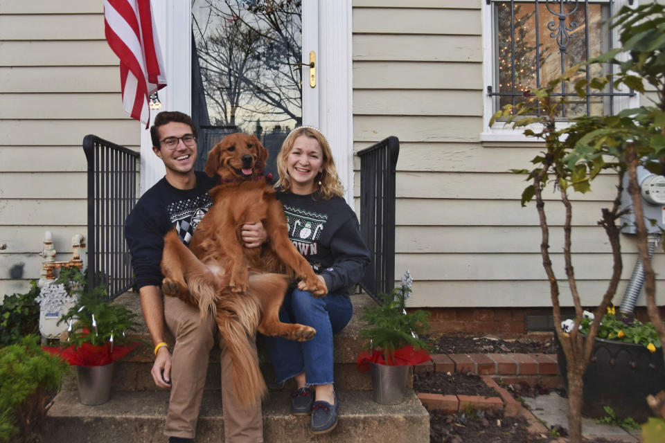 "In this photo provided by Olivia Hinerfeld, Olivia Hinerfeld poses with her boyfriend, Ryan Shymansky, and their golden retriever Lincoln on Dec. 6, 2020, in Washington. Jealous of the attention that Hinerfeld is paying to her video conference call, Lincoln,will fetch ""the most disgusting"" tennis ball he can find from his toy crate to drop into the lap of the Georgetown University Law School student. (Olivia Hinerfeld via AP)"