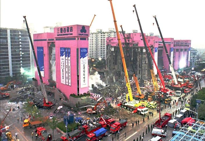 Using cranes to lift heavy debris, crews hunt for survivors and bodies following the June 29, 1995, collapse of Seoul's Sampoong Department Store. More than 500 died.