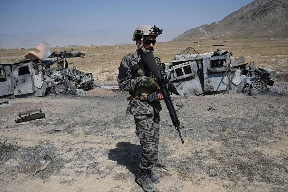 A member of the Taliban Badri 313 military unit stands besides damaged vehicles near Kabul (AFP via Getty Images)
