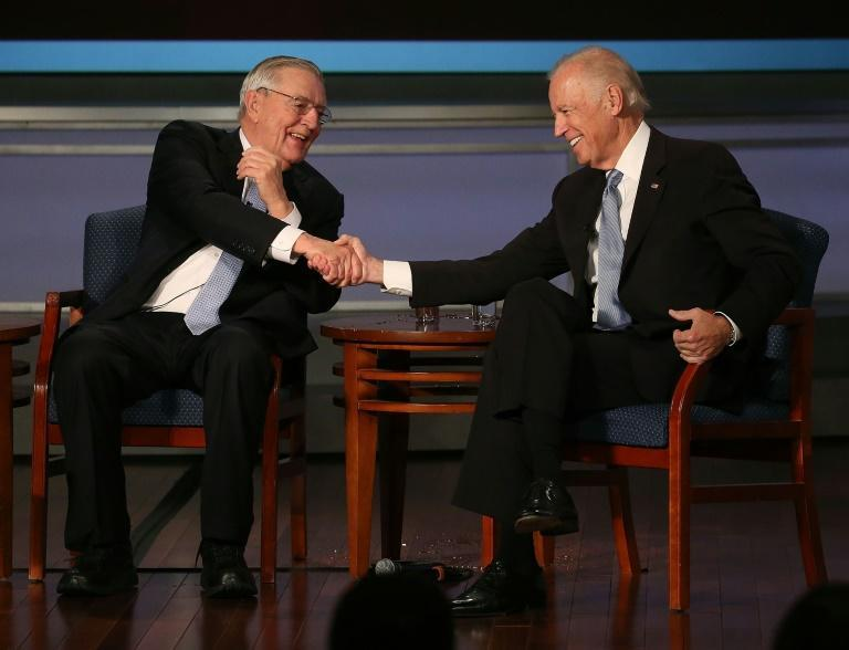 US then-Vice President Joe Biden (R) shakes hands with former Vice President Walter Mondale during an event in October 2015 in Washington, DC